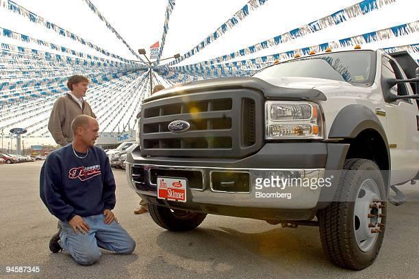 Sales associate Chris Stephens, rear, shows a F550 Ford truck to David Carter, kneeling, at the Jim Skinner Ford Dealership in Birmingham, Alabama...
