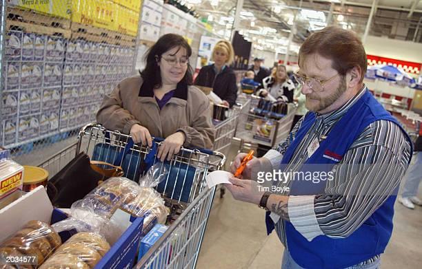 Sales associate Don Ebert checks a shopper's purchase March 8 2002 at a Costco Wholesale store in Niles Illinois Warehouse retailer Costco Wholesale...