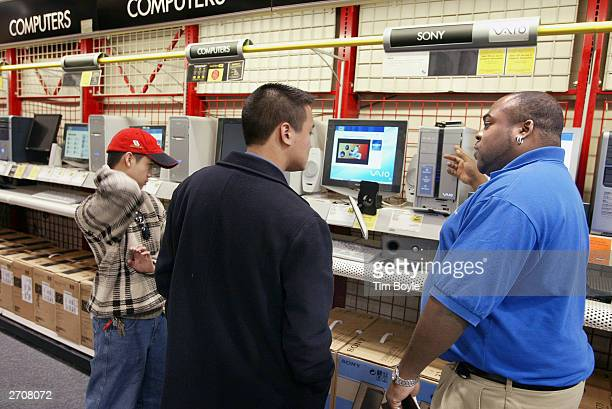 Sales associate Mark Macklin assists computer shoppers at a Best Buy store November 7 2003 in Skokie Illinois The Bureau of Labor Statistics of the...