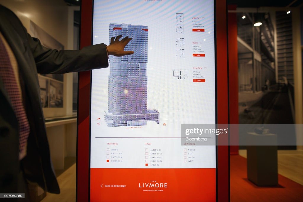 A sales associate points to a screen displaying a rendering of the GWL Realty Advisors Livmore luxury apartment building in Toronto, Ontario, Canada, on Tuesday, July 10, 2018. Toronto's rental market is going upscale to meet surging demand from millennials and downsizing baby boomers who want a little more than your average walkup while providing a steady income stream for institutions such as pension funds. Photographer: Cole Burston/Bloomberg via Getty Images