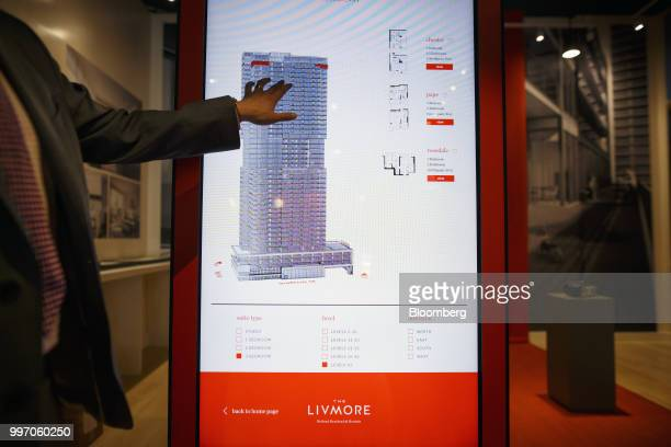 A sales associate points to a screen displaying a rendering of the GWL Realty Advisors Livmore luxury apartment building in Toronto Ontario Canada on...