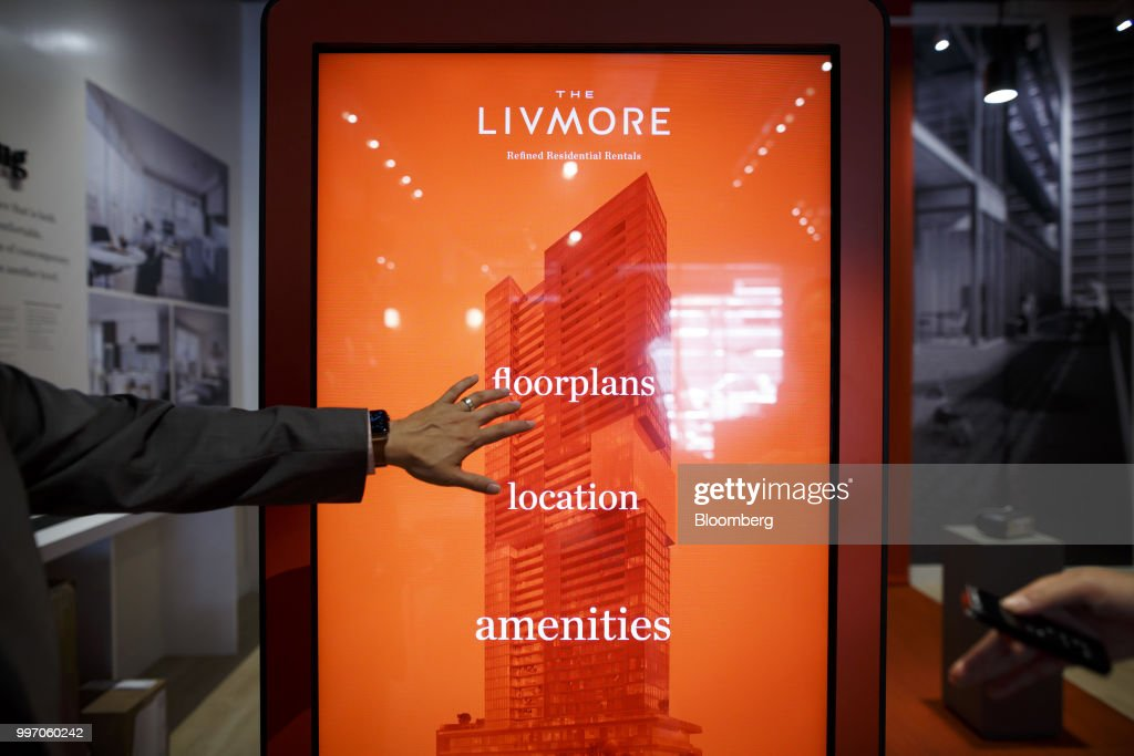 A sales associate points to a screen displaying information about the GWL Realty Advisors Livmore luxury apartment building in Toronto, Ontario, Canada, on Tuesday, July 10, 2018. Toronto's rental market is going upscale to meet surging demand from millennials and downsizing baby boomers who want a little more than your average walkup while providing a steady income stream for institutions such as pension funds. Photographer: Cole Burston/Bloomberg via Getty Images
