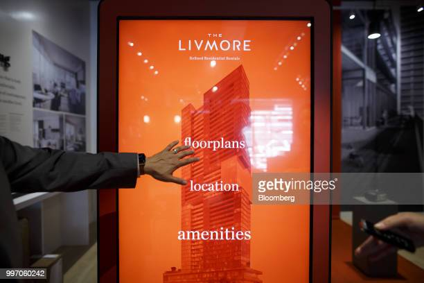 A sales associate points to a screen displaying information about the GWL Realty Advisors Livmore luxury apartment building in Toronto Ontario Canada...