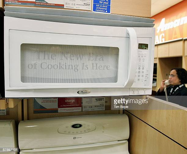 Sales associate Shaista Ansari talks on the phone near a Whirlpool microwave and a Maytag range at a Sears store May 12 2006 in Niles Illinois...
