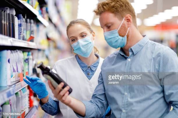 sales clerk advising customer on beauty product - face mask beauty product stock pictures, royalty-free photos & images