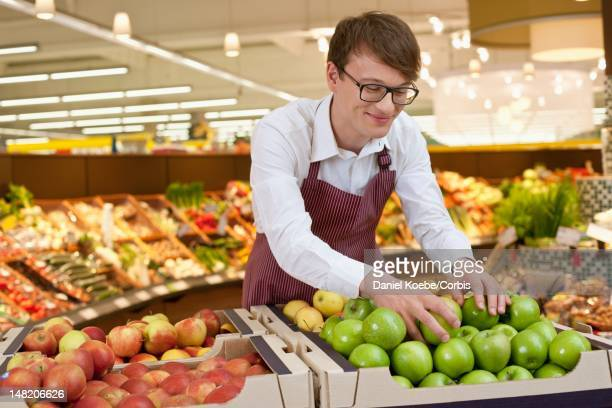 sales clerk arranging apples in supermarket - arranging stock pictures, royalty-free photos & images
