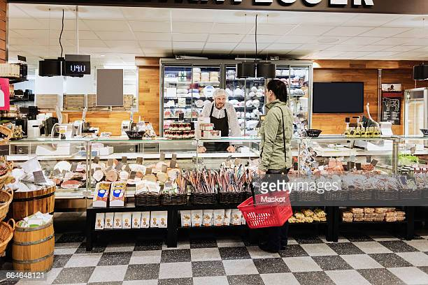 sales clerk assisting woman while standing in supermarket - delicatessen stock photos and pictures