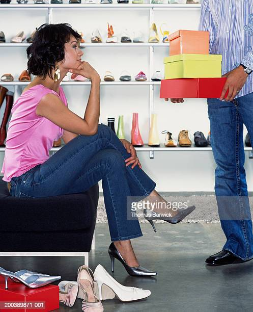 sales clerk assisting young woman in shoe store, side view - シューズボックス ストックフォトと画像