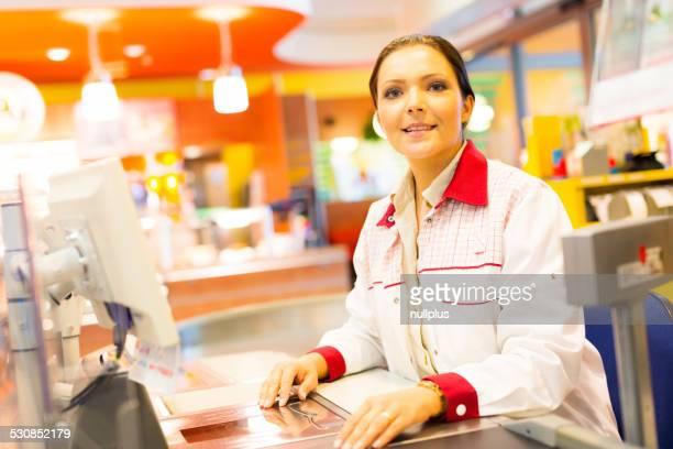 sales clerk at a cash register in the supermarket