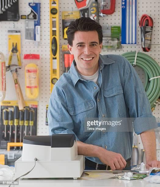 Sales clerk behind counter at hardware store