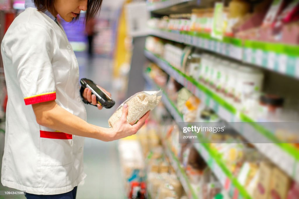 Latin American Sales Clerk At A Supermarket Suggesting A