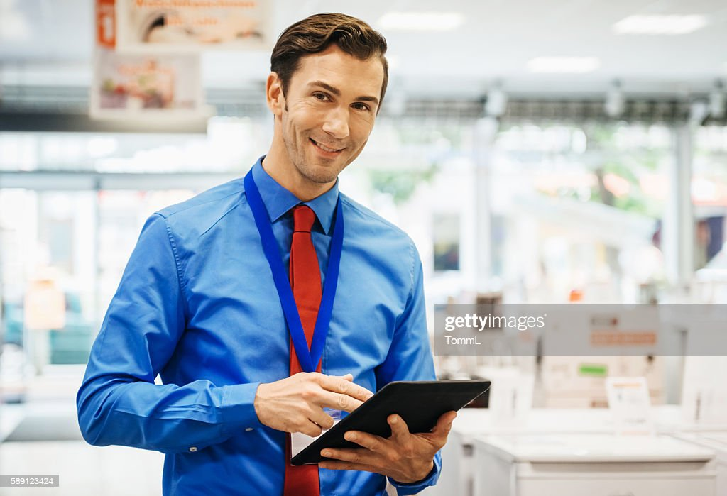 Sales clerk doing online order with tablet pc : Stock Photo