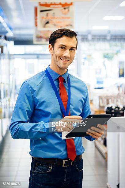 sales clerk doing online order with tablet pc - electronics store stock photos and pictures