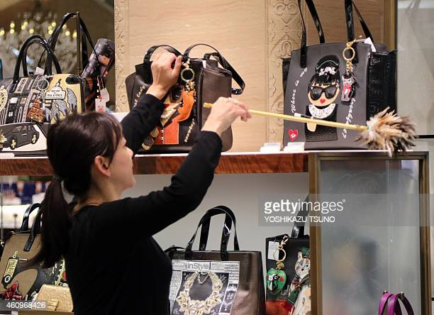 A sales clerk dusts a shelf of bags to greet New Year shoppers at a department store in Tokyo on January 2 2015 AFP PHOTO / Yoshikazu TSUNO
