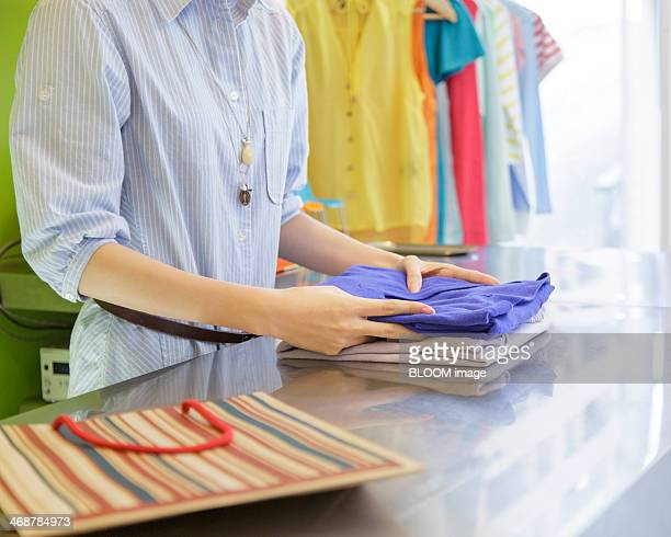 Sales clerk folding sweater on counter