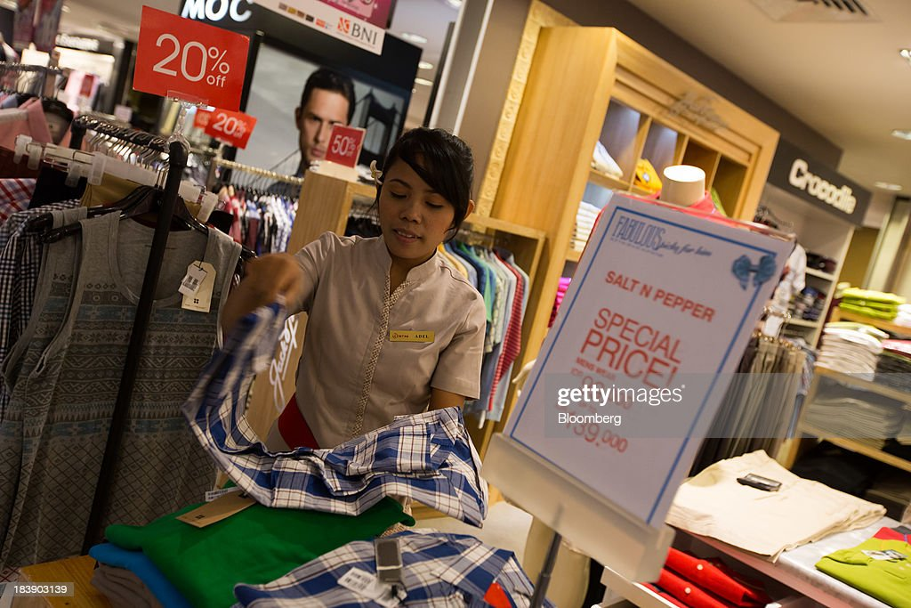 A sales clerk folds clothing at the Discovery Shopping Mall
