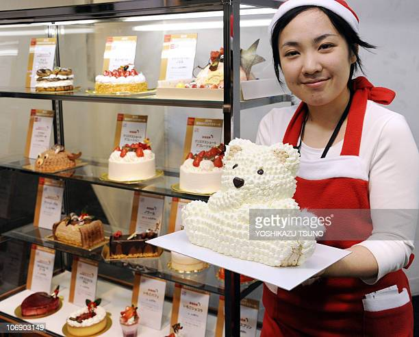 A sales clerk from Seibu department store displays a white chocolate polar bear cake at a Christmas cake collection preview in Tokyo on November 16...