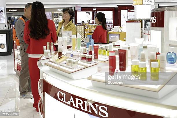 A sales clerk front helps customers at the Clarins Group booth at the cosmetics section of the Lotte Duty Free Shop in the Tokyu Plaza Ginza shopping...