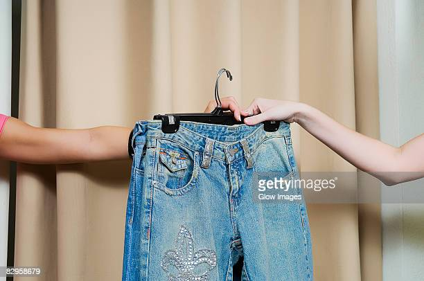 sales clerk giving a jeans to a customer's hand - jeans calça comprida - fotografias e filmes do acervo