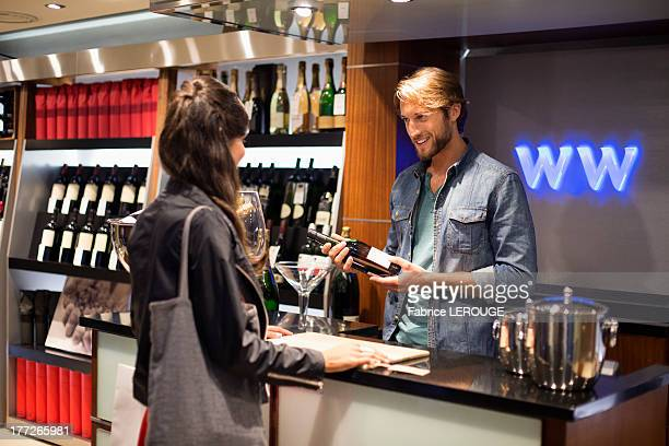 Sales clerk giving a wine bottle to a customer