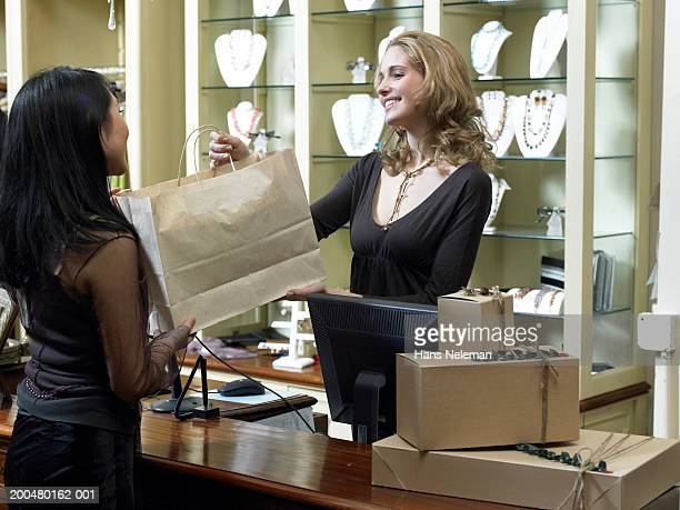 Sales clerk handing young woman shopping bag