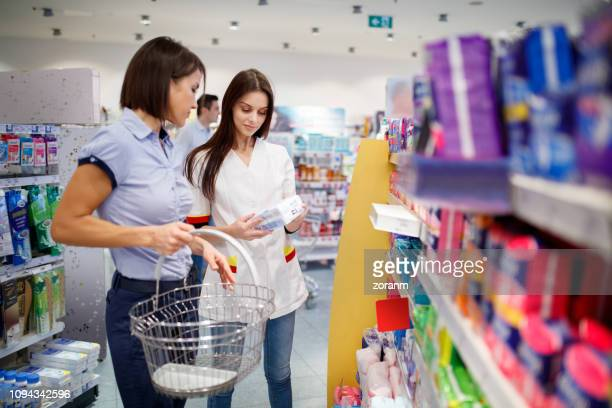 sales clerk helping customer choose sanitary pads - toiletries stock pictures, royalty-free photos & images