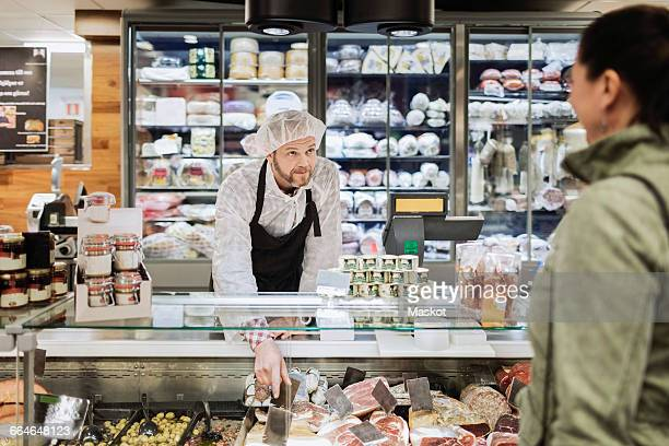 sales clerk looking at female customer while assisting at supermarket - delicatessen stock pictures, royalty-free photos & images