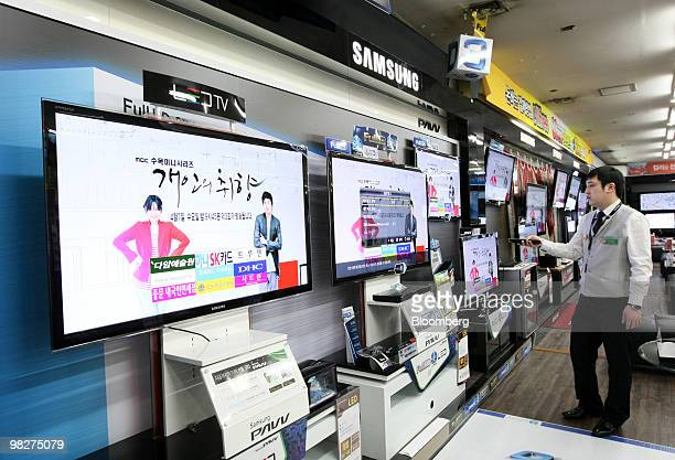 A sales clerk looks at light emitting diodes televisions at Samsung Electronics Co's store in Seoul South Korea on Tuesday April 6 2010 Samsung...
