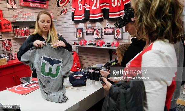 Sales clerk Melanie Crete left bags up a Hartford Whalers Tshirt for Carolina Hurricanes fans Lawrence Miller second from right his wife Jennifer...