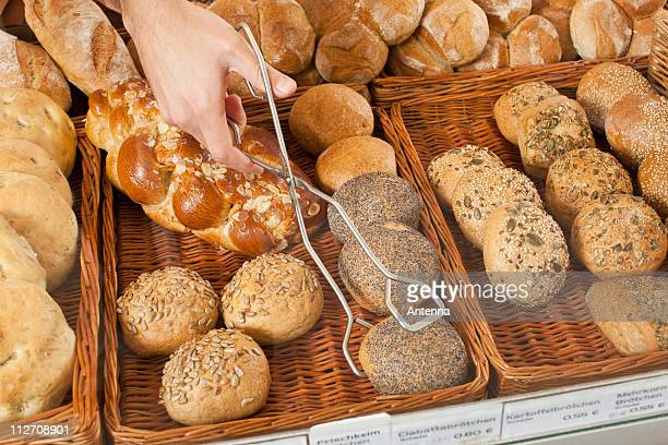 A sales clerk picking up a roll with tongs in a bakery, focus on hand