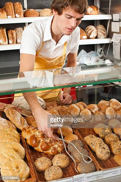 A sales clerk picking up a roll with tongs in a bakery