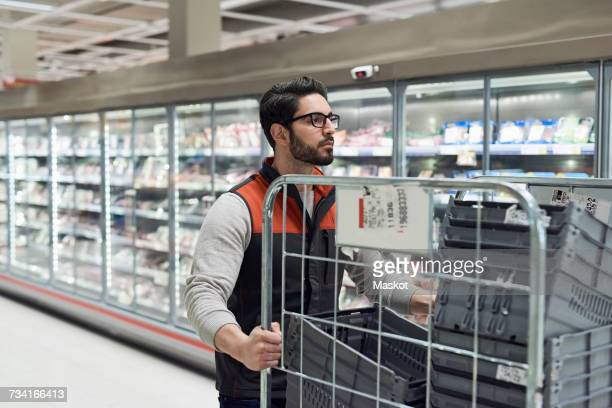 Sales clerk pushing cart with plastic crates at refrigerated section in supermarket