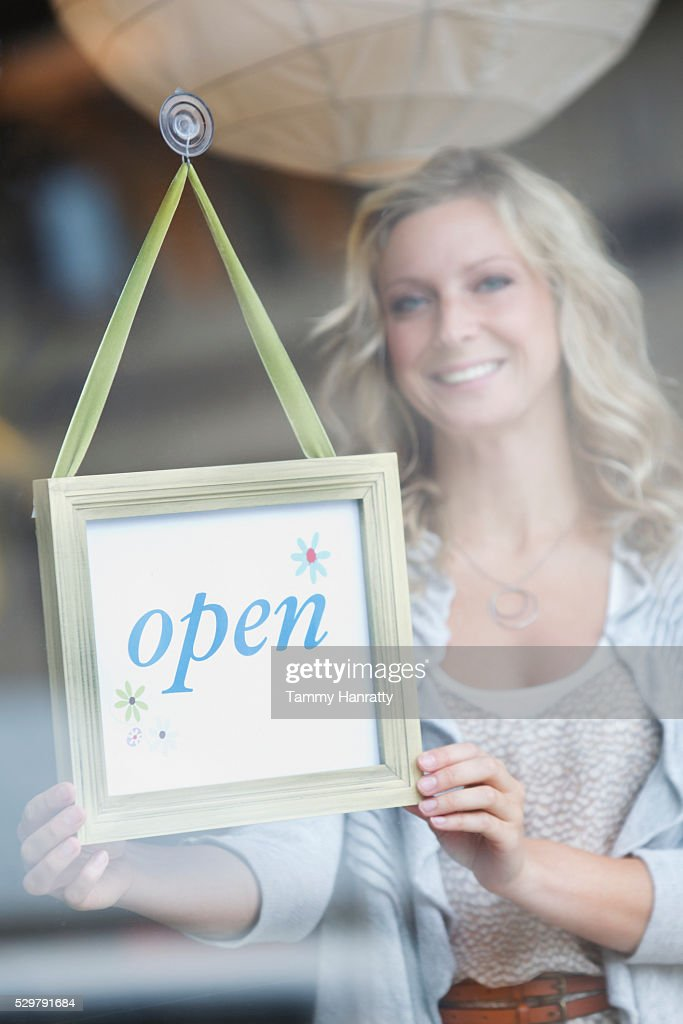 Sales clerk putting up open sign : Stock Photo