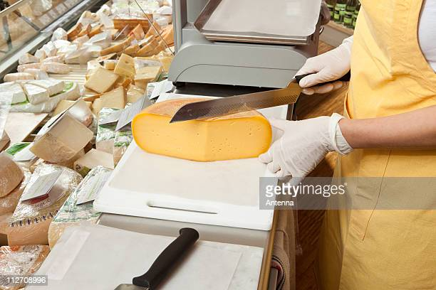 A sales clerk slicing cheese at the cheese counter