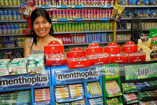 Sales clerk smiling at counter in a convenience store in Avenida San Juan