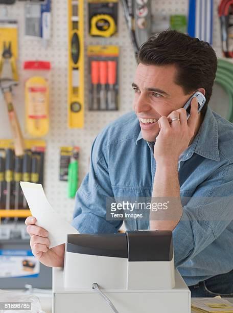 Sales clerk talking on telephone in hardware store