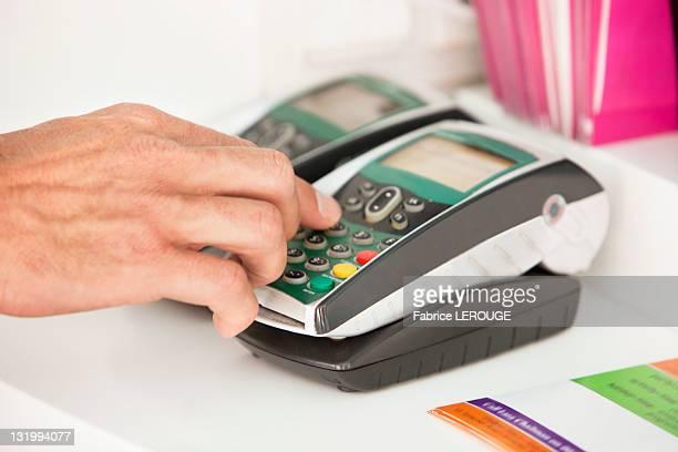 Sales clerk using a credit card reader at counter