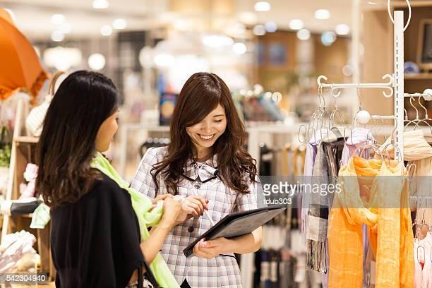 Aushilfsverkäufer mit einem Digitaltablett um den Kunden