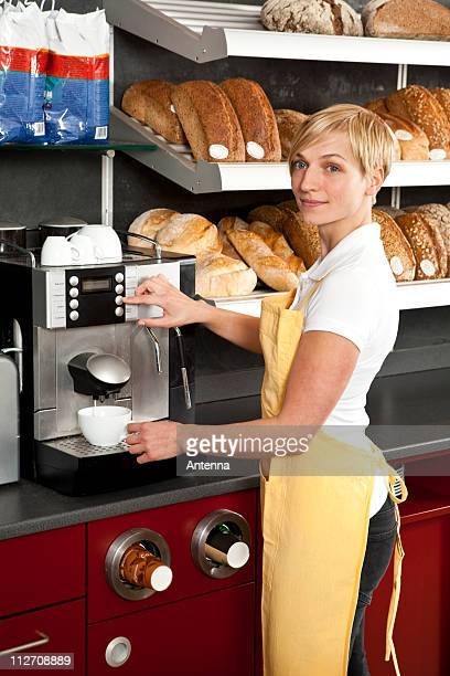 A sales clerk using an espresso maker in a bakery cafe