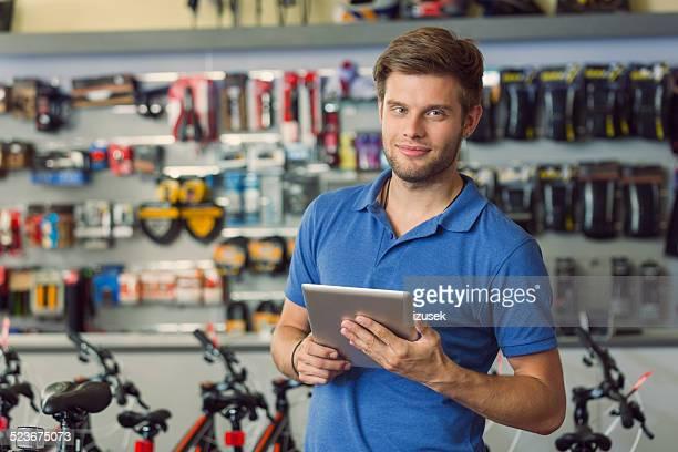 Sales clerk with digital tablet in bike shop