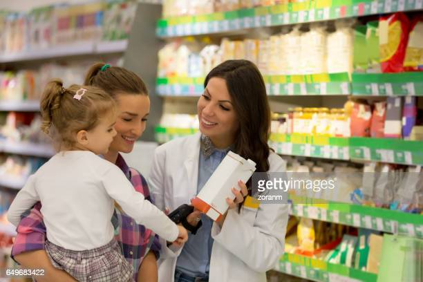 sales clerk with mother and daughter - juice carton stock photos and pictures