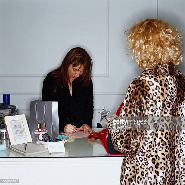 sales clerk writing receipt while customer waits - レシピ帳 ストックフォトと画像