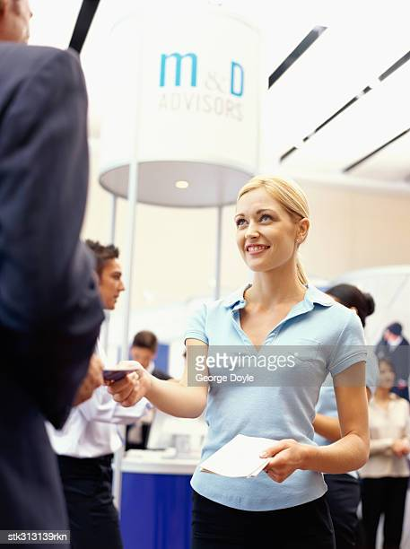 sales executive giving brochure to a businessman at an exhibition