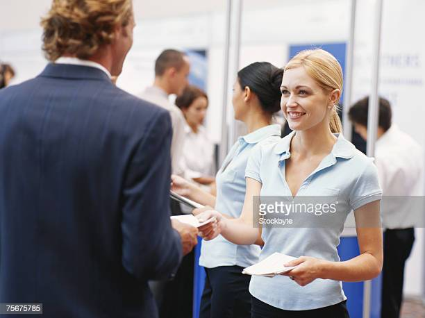 Sales executive giving brochures to businessman at exhibition