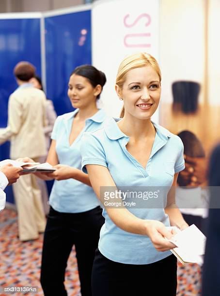 sales executives distributing brochures at an exhibition