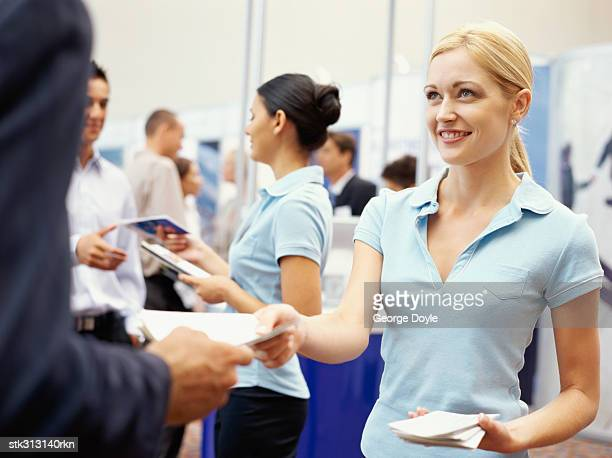 sales executives distributing brochures to business executives at an exhibition - tradeshow stock pictures, royalty-free photos & images