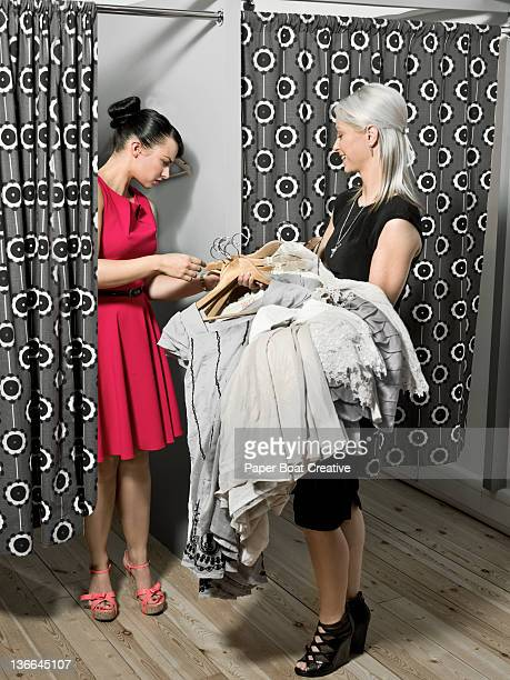 sales lady offering a bunch of new dresses to try