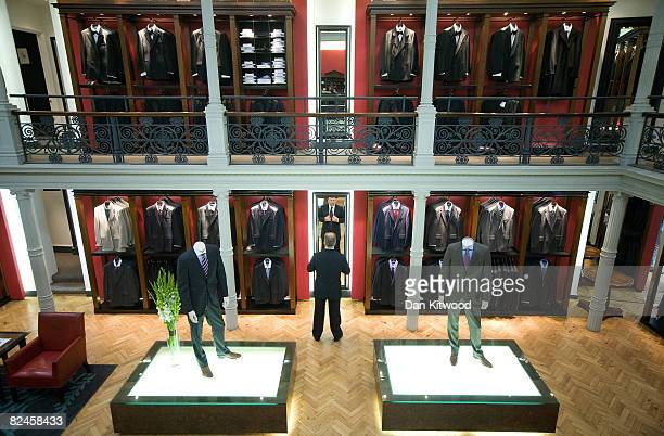 A sales man adjusts his shirt at Gieves and Hawkes at No 1 Savile Row on August 18 2008 in London England A bespoke two piece suit takes up to eight...