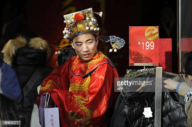 A sales man dressed as the god of wealth waits for customers at a sales promotion for the upcoming Lunar New Year at the entrance of a clothing store...
