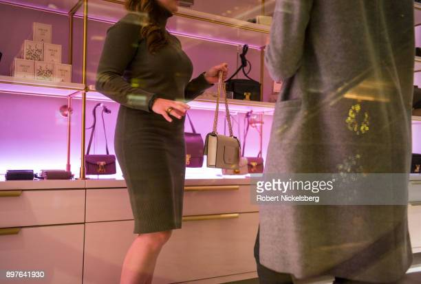 A sales person sells an Ivanka Trump handbag to a customer inside Trump Tower December 18 2017 in New York City Tourism along 5th Avenue in front of...